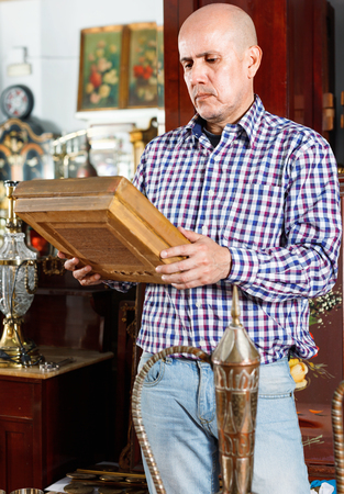 Portrait of mature pleasant man choosing vintage goods at antiques shop