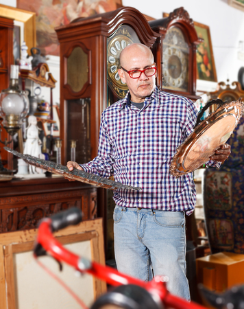 Interested adult male collector of rare items choosing ancient things in antique shop