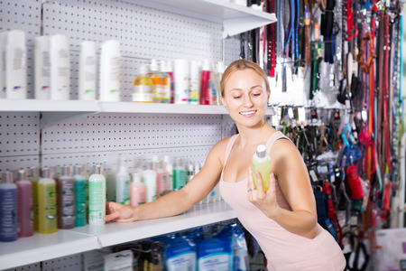 Cheerful girl examining shelves with pet shampoo in pet shop