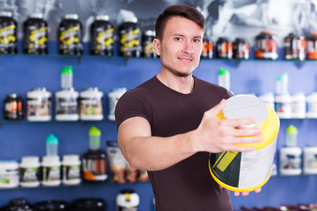Young muscular guy looking sport nutrition products in store, reading content label