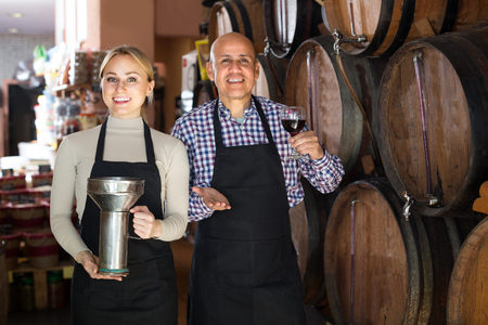 american man and woman wearing apron holding wine vessels in wine house