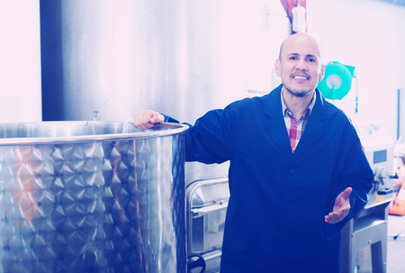 Smiling mature worker man standing in winery production section