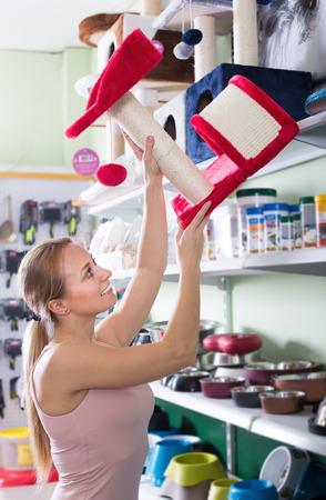 Young woman examining pretty cat houses in pet shop Фото со стока - 119989735