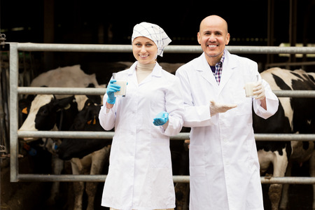 Portrait of two smiling veterinarians wearing white coats and having a glass with fresh milk in cowshed