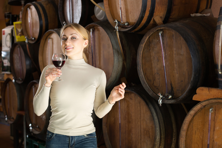 Friendly smiling young woman tasting wine from wood in wine cellar