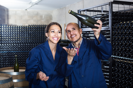 happy russian man and women coworkers looking at bubbly wine in bottle standing in wine cellar