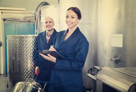 Portrait of cheerful positive diligent expert woman standing with clipboard and male winemaker in wine processing section Stockfoto