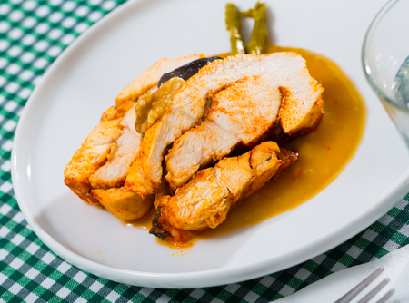 Delicious savory turkey breast served on white plate in mango sauce with prune, walnut and pickled asparagus