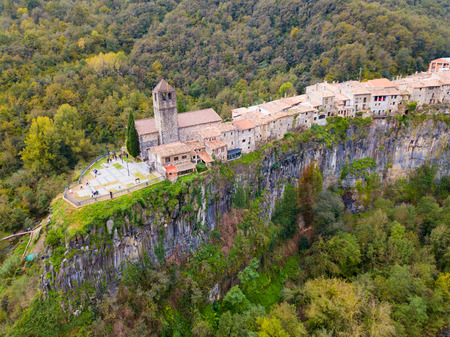 Picturesque forest landscape with medieval village of Castellfollit de la Roca on rocky cliff, Spain Imagens