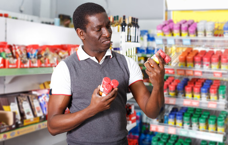 Positive young African man choosing spice in grocery store