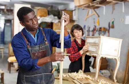 Portrait of male and female restorers working with wooden details in furniture workshop
