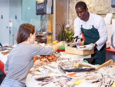 Positive salesman proposing young woman raw clams at fish market