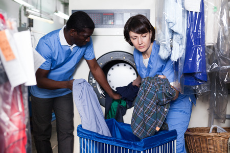 Skilled female laundry worker with her African male colleague loading washing machine with dirty clothes