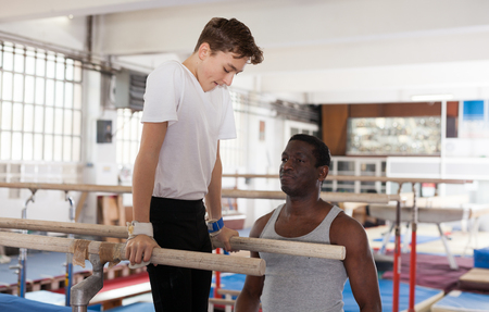 Male coach training teenage boy on gymnastic equipment at acrobatic hall