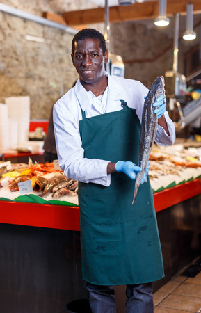 Portrait of African American salesman working at showcase with seafood