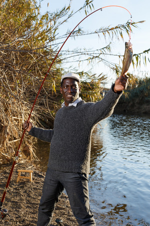 Mature African man standing near river and pulling fish on hook 免版税图像