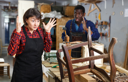 Outraged woman restorer standing near vintage armchair at workshop