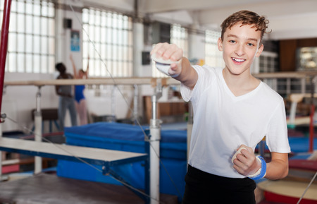 Portrait of cheerful teenage boy in gymnastic swimsuit at acrobatic center