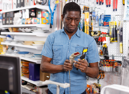 Active African American salesman working on computer behind counter in store of household goods Stok Fotoğraf