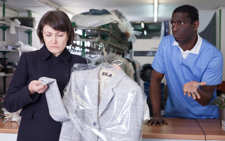 Portrait of dissatisfied young woman customer of modern dry cleaning