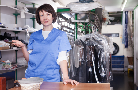 Polite female worker welcoming in modern dry cleaning salon standing at reception counter