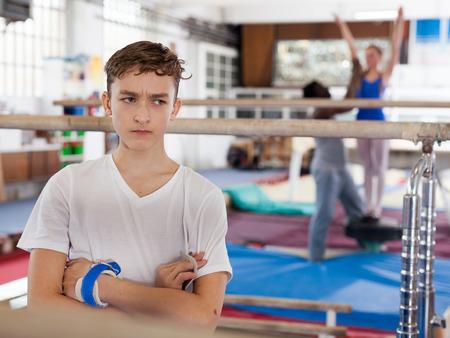 Portrait of sad teenage athlete standing near gymnastic equipment at acrobatic hall