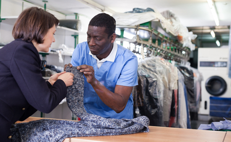 African-American man worker of laundry taking clothes for dry cleaning from female client