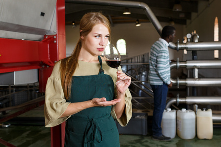 Portrait of young woman winemaker checking red wine in glass at winery