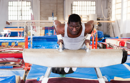portrait of afro man in sportswear doing exercises on pommel horse in acrobatic hall