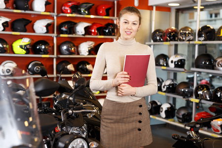 positive confident woman shopping assistant standing in motorcycle store