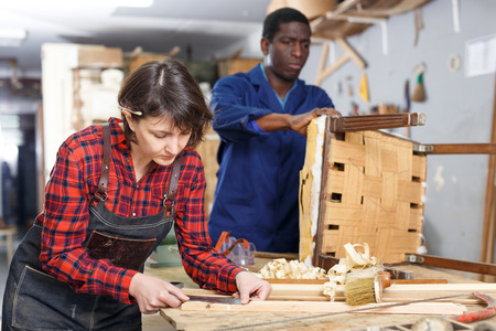 Woman and man carpenters using tools for restoration wooden chair in studio