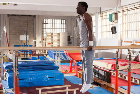 Portrait of adult african man training on parallel bars at acrobatic center