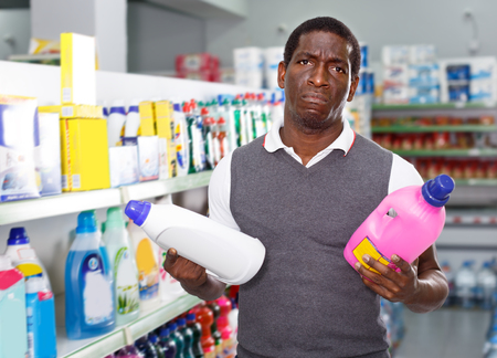 sad African man holding bottle of household chemicals in big store Stock Photo