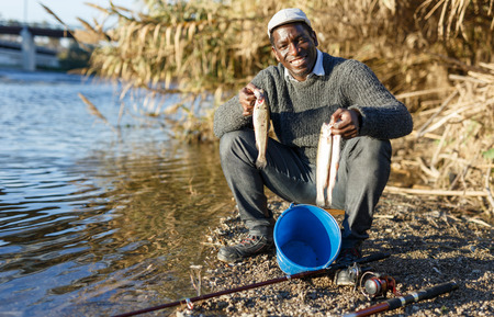 Friendly mature Afro fisherman sitting on stool and holding fish