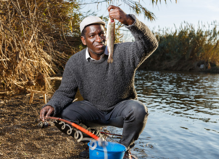 Portrait of African man fishing on river and putting caught fish in bucket 免版税图像