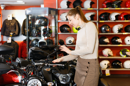 Positive happy cheerful young woman in moto salon choosing motorcycle to buy