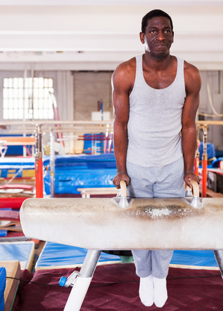 Portrait of adult african man training on pommel horse at acrobatic center Foto de archivo - 120055414