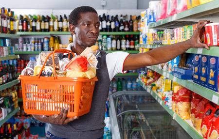 Alegre hombre afro sonriente positivo con carrito de compras eligiendo productos en la tienda de comestibles