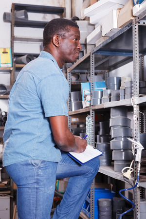 Confident African American salesman taking inventory of goods in building materials store Stock fotó