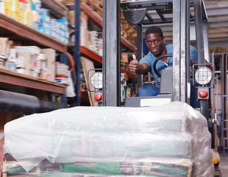 Young African American male operator of forklift working in shop of building materials