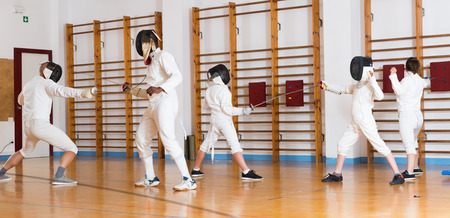 Adults and teens wearing fencing uniform practicing with a foil in gym