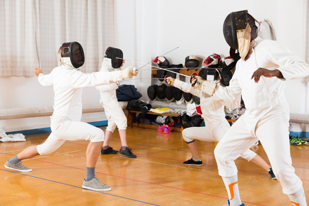 Cheerful group practicing effective fencing techniques in sparring in training room