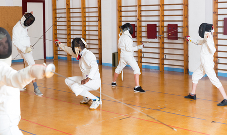 Group of kids and adults fencers with trainer engaged in fencing in gym Standard-Bild