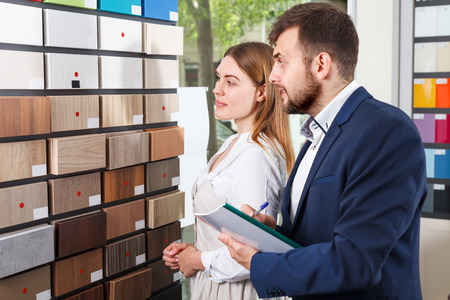 Adult girl consulting with salesman in furniture salon Stok Fotoğraf