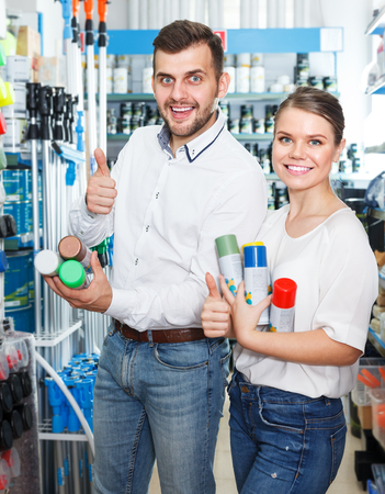 Young family pair choosing paint spray together in paints shop. Focus on man