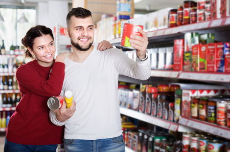 Happy clients buying tinned food at grocery store