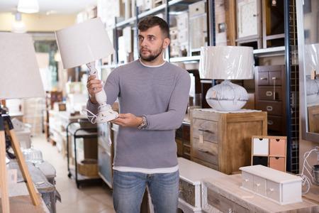 Beau jeune homme à la recherche d'une lampe de table élégante dans un magasin de meubles d'occasion
