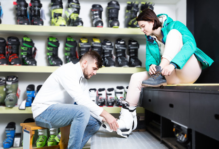 Bearded guy helping happy girlfriend to trying on ski boots in store of sports equipment