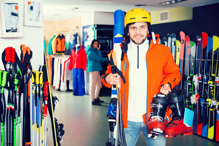Smiling sporty young  male standing with purchased ski equipment in shop