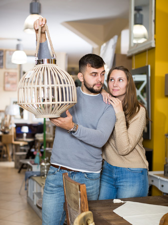 Happy couple with vintage suspended lamp in apartment crowded of old furniture Foto de archivo
